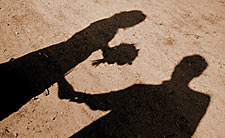 married couple with cast shadow on ground with bouquet